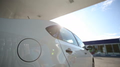A man fills a white car quality biofuels at sunrise Stock Footage
