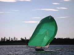 dinghy sailboat sailing on a lake under a blue sky - stock photo