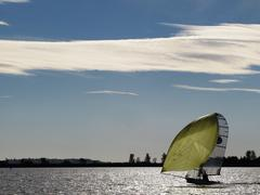 a small dinghy with large yellow sail under a blue sky sailing on a lake - stock photo