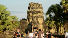 Zoom Out - Tourists walk towards the Main Temple - Angkor Wat Cambodia Stock Footage