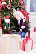 Boy with interest looks at christmas gifts and the wooden nutcracker Stock Photos
