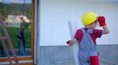 Little worker in front of house, fix protective glasses Stock Footage