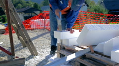 Sawing styrofoam and checking measures Stock Footage