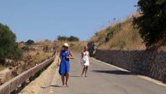 Two girls on a rural road down the hill. Sicily - stock footage