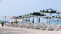 Idyllic Scene of Deck Chairs under an Umbrella on the Beach. Stock Footage