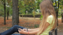 Sad Teen Girl Texting, Using Smartphone On Park Bench HD Stock Footage