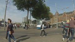 Trams come and go outisde Centraal Station Amsterdam Stock Footage