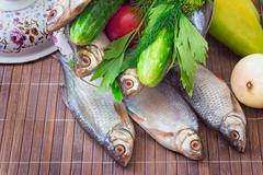 Fish and components for her preparation: vegetables, spices, parsley. Stock Photos