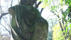 Pan up and down of Jesus stone statue in a graveyard, in the sun silhouette Stock Footage