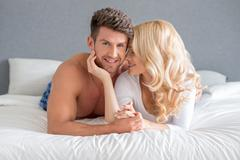 Sweet Young White Couple Lying on Bed Stock Photos