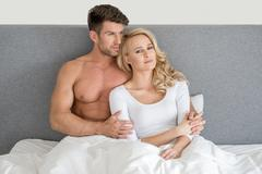 Middle Age Romantic Couple on Bed Fashion Shoot Stock Photos