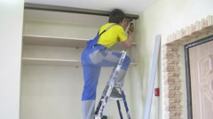 Young workers assemble a closet in a niche in room, time lapse Stock Footage