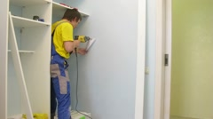 Workers assemble a wardrobe in the room, camera rotates Stock Footage