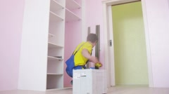 Workers assemble a wardrobe in the room with pink walls Stock Footage