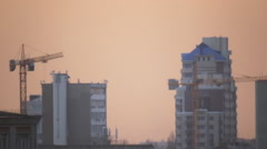 Building site with cranes on darkening sky Stock Footage