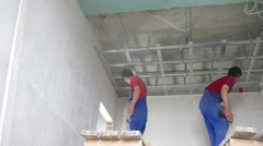 Stock Video Footage of workers assemble ceiling mount for suspended ceiling using level