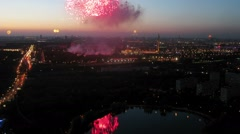Fireworks flashes and sparks above city with pond and traffic Stock Footage