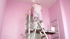 Worker on a ladder to paint the walls in pink above the doorway - stock footage