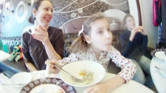 Mother and daughter sitting at the table, eating and drinking tea Stock Footage