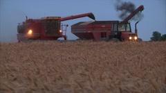 Combine as grain cart pulls away Stock Footage