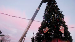 Workers in cabin of hoisting machine adorns christmas tree - stock footage