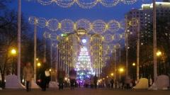 Illuminated christmas tree shines on boulevard with people Stock Footage
