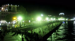 People make a promenade on the waterfront at night in summer Stock Footage