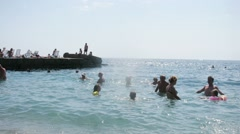 Adults and children bathe in the sea near the waterfront Stock Footage