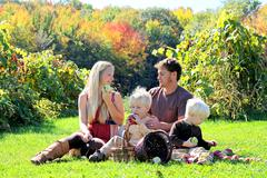 happy family of four having fruit snack at autumn apple orchard - stock photo