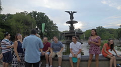 Tourists Statue Central Park Angel Sculpture Wings Pond NYC 4K New York City Stock Footage