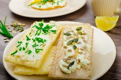 crisp crispbread with cheese spread with chives and crisp crispbread with cur - stock photo