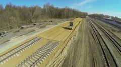 Construction site of railway with road roller flattens sand Stock Footage