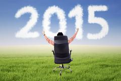 Male entrepreneur on chair with number 2015 Stock Illustration