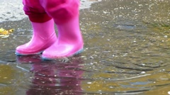 Small girl feet in pink rubber boots sploshing in puddle - stock footage