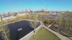 Small pond in park near oil refinery in sunny spring day Stock Footage