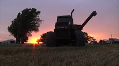Tractor and grain cart pull away at sunset Stock Footage