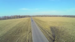 Minivan passes by road among fields at sunny spring day Stock Footage