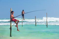 Young stilt fishermen at hikkaduwa beach. Stock Photos