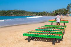 Local worker putting colourful wooden deck chairs on beach Stock Photos