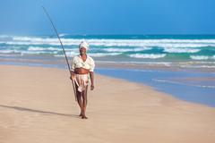 Elderly stilt fisherman at hikkaduwa beach. Stock Photos