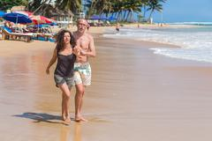 Tourist  couple walk on sandy beach Stock Photos