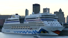 4K UHD - Small yacht cruising in front of giant cruise ship in city port Stock Footage