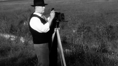 forties photographer in front of a stream black and white - stock footage