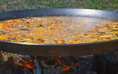 Paella cooking a wood fire Stock Photos