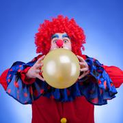 Stock Photo of clown in red costume with balloon in hands