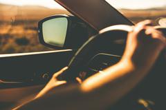 hands on steering wheel summer trip closeup. - stock photo