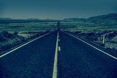 down the road. straight desert highway in bluish color - stock photo