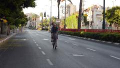 Mature man bikes in car-less city - stock footage