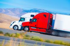 Two speeding semi trucks on the nevada highway, usa. trucking in america. Stock Photos