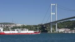 Orange merchant crude oil tanker ship crossing Bosporus Bridge Stock Footage